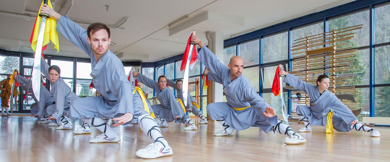 Kung Fu Athleten und Athletinnen zeigen eine Schwertform.