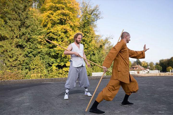Kung Fu Intensiv Wochenende im Shaolin Chan Tempel Luzern - Schweiz. Ein Meister zeigt einem Schüler eine Stockform.