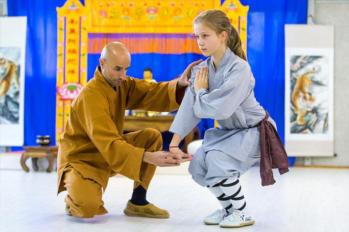 Shaolin Kung Fu Meister Shi Yong Lin, Salvi Ferrara, korrigiert eine Schülerin im Kinderunterricht im Shaolin Chan Tempel Institut Aargau - Schweiz.