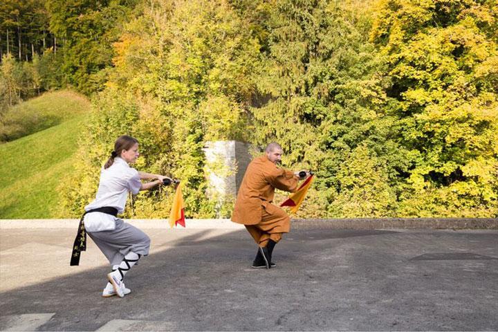 Wochenaufenthalt Unterricht im Shaolin Chan Tempel Luzern - Schweiz. Shaolin Kung Fu Meister Shi Yong Wen, Thomas Degen, zeigt einer Schülerin eine Säbelform.