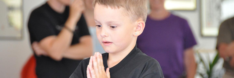Kind macht Anjali Mudra, auch bekannt als Namaste Geste.
