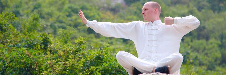 Mann macht eine Qi Gong Übung auf einem Felsen.