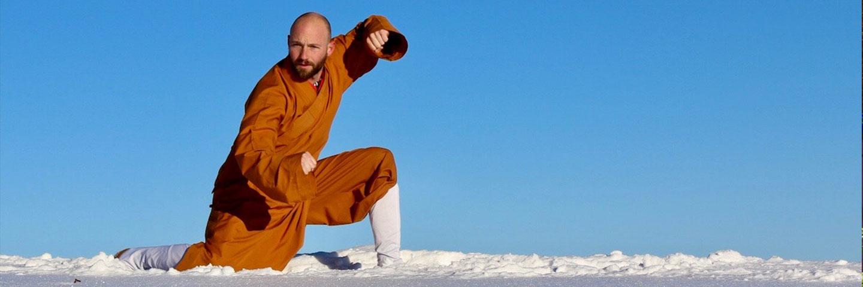 Shaolin Kung Fu Grossmeister Shi Xing Long, Roger Stutz, zeigt eine traditionelle Stellung im Schnee bei klarem Himmel.