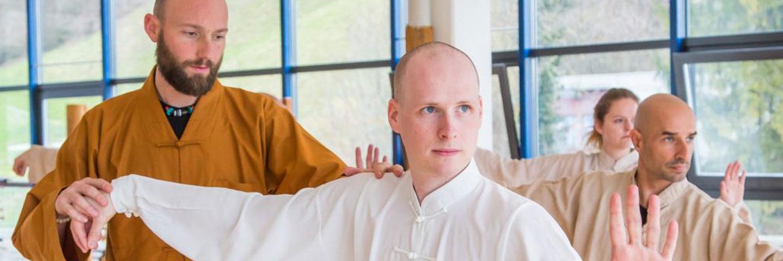 Meister korrigiert eine Stellung bei einem Taiji Übenden.
