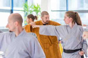 Gruppenunterricht im Shaolin Chan Tempel Luzern - Schweiz. Meister Shi Yong Wen, Thomas Degen, korrigiert eine Schülerin.
