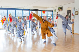 Gruppenunterricht im Shaolin Chan Tempel Luzern/Schweiz. Es wird eine Säbelform gezeigt. Shaolin Kung Fu Grossmeister Shi Xing Long (Roger Stutz) ist im Vordergrund zu sehen.