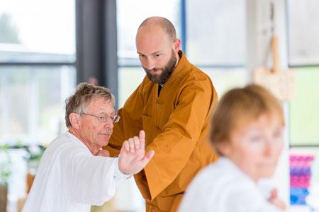 Shaolin Kung Fu Grossmeister Shi Xing Long, Roger Stutz, korrigiert einen Qi Gong Teilnehmer eines Seminars.