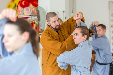 Shaolin Kung Fu Meister Shi Yong Wen, Thomas Degen, korrigiert eine fortgeschrittene Schülerin.