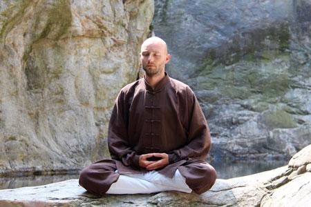 Shaolin Kung Fu Grossmeister Shi Xing Long, Roger Stutz, bei der Meditation in der Natur. Die Hände liegen im dhyana Mudra.