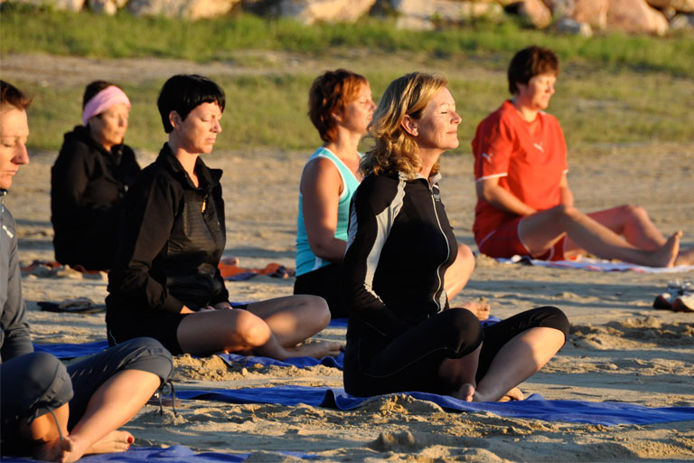 Mitglieder des Shaolin Chan Tempels Luzern -Schweiz bei der Meditation an einem Strand.