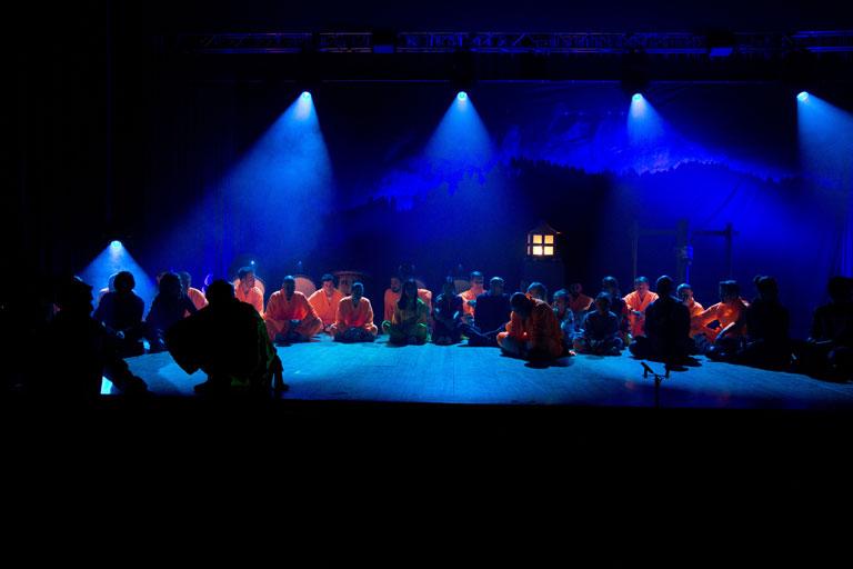 Jubiläumsshow des Shaolin Chan Tempels Luzern - Schweiz. Teilnehmer sitzen bei abgedunkeltem Licht auf der Bühne.