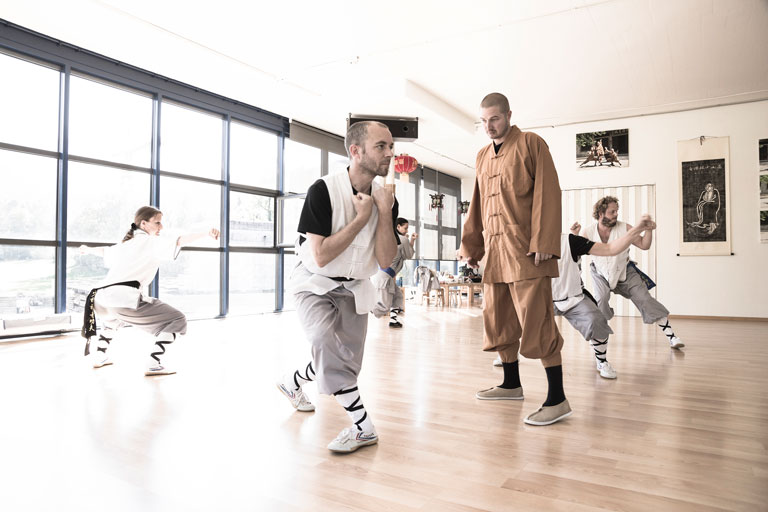 Gruppenunterricht im Shaolin Chan Tempel Luzern - Schweiz. Kung Fu Meister Shi Yong Wen, Thomas Degen, begutachtet den Fortschritt eines Schülers.