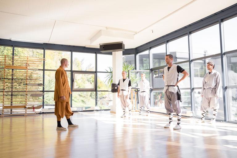Gruppenunterricht im Shaolin Chan Tempel Luzern - Schweiz. Kung Fu Schüler hören den Anweisungen des Instruktors zu.