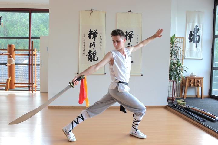 Noah Arfini zeigt Kung Fu Form mit Säbel.