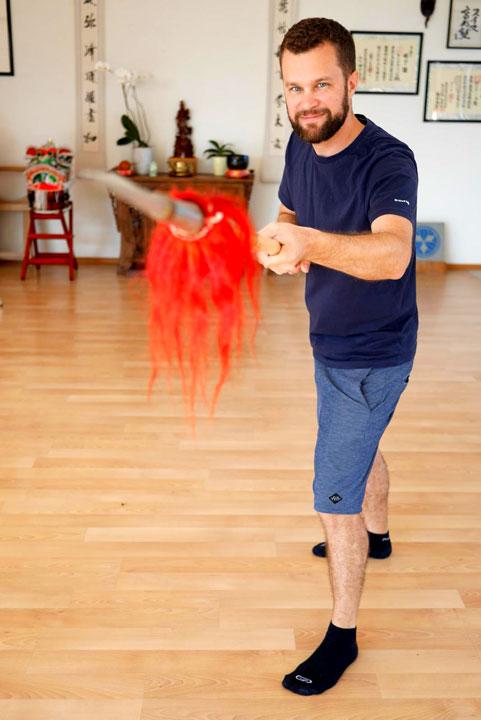 Ein Teilnehmer hält einen Speer in der Hand - Anlass ist ein Kundenevent von Siemens im Shaolin Chan Tempel Schweiz