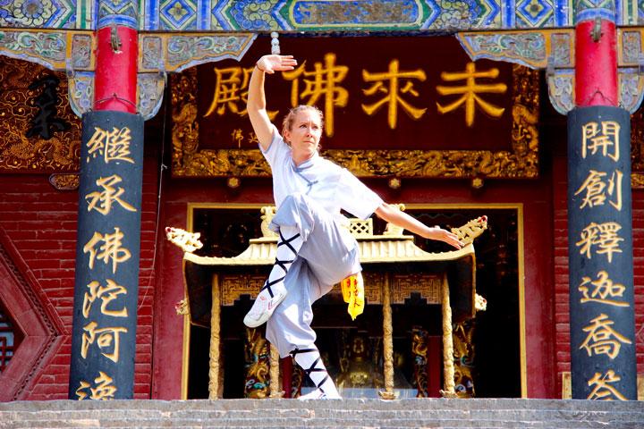 Lin Yue zeigt Kung Fu Form vor Tempel.