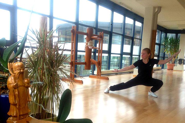 Eine Kung Fu Athletin macht einen tiefen Stand.