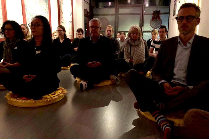 Kuoni Mitarbeiter und Kunden bei der Meditation.