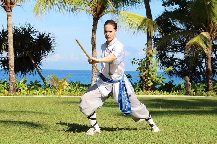 Kung Fu Kämpferin am Strand mit einem Stock.