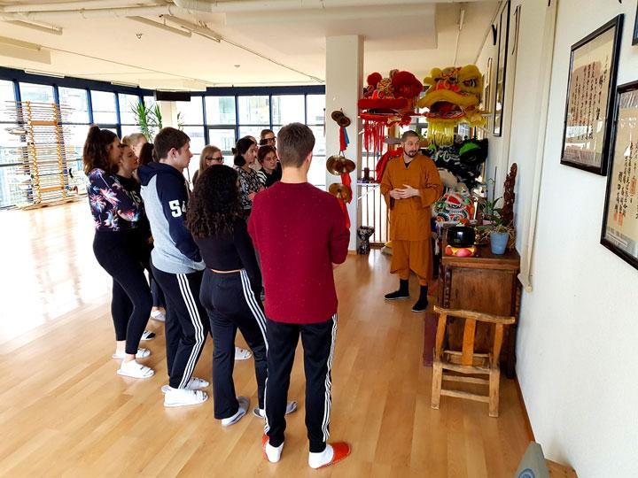 Thomas Degen erklärt SchülerInnen etwas über Buddhismus.