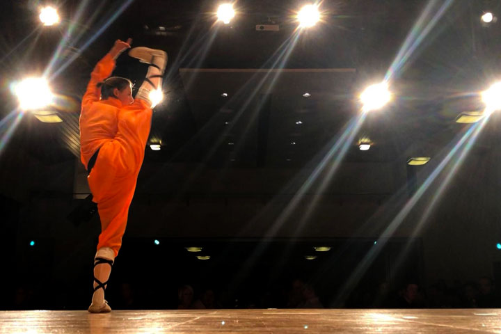 Eine Athletin macht einen fallenden Spagat auf der Bühne.