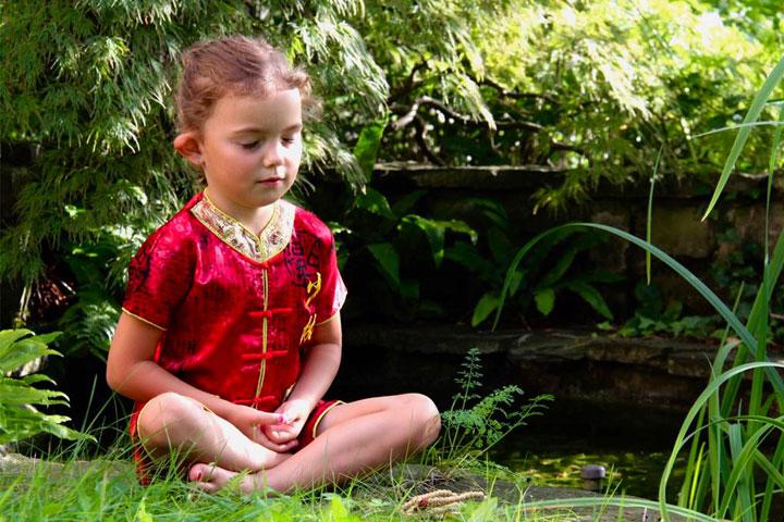 Kind meditiert an einem Fluss