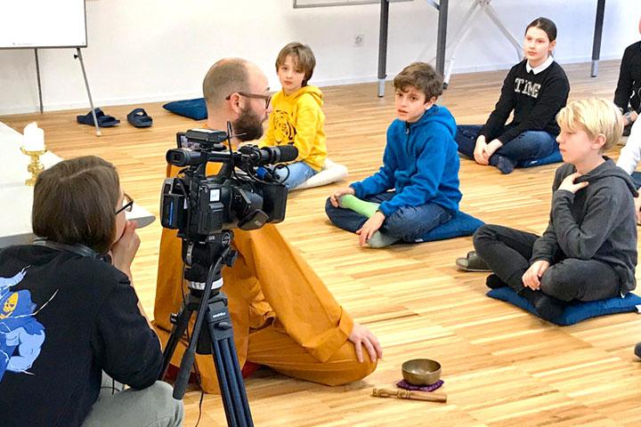 Tele 1 Nachrichten Team filmt Schulklasse bei Meditation
