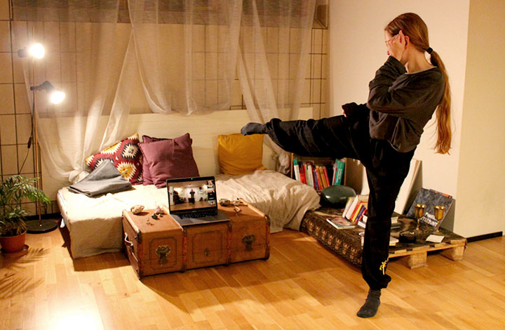 Frau macht Kung Fu vor Fernseher.