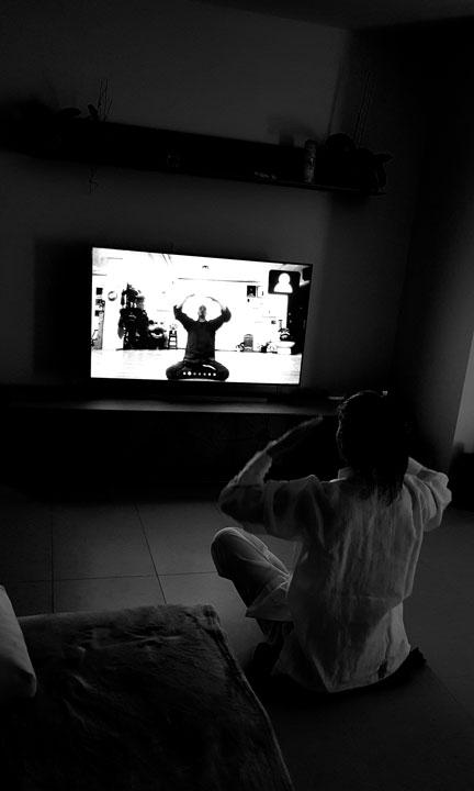 Frau macht Qi Gong vor Fernseher.