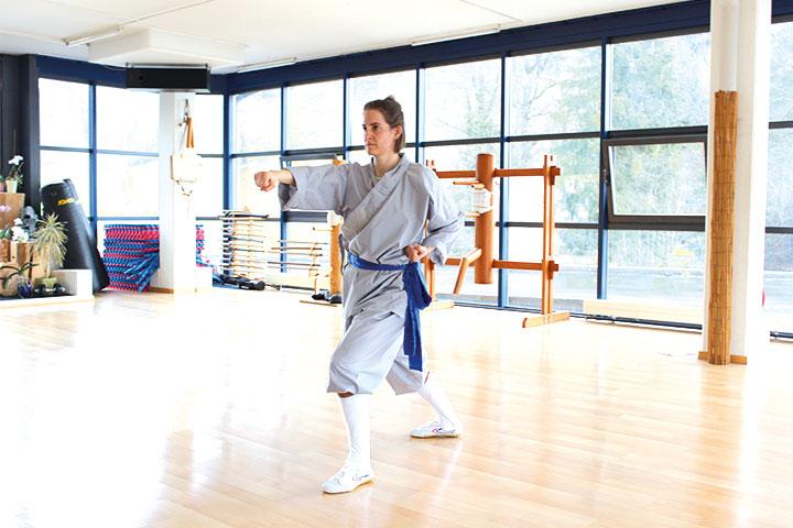 Trainingsraum im Shaolin chan Tempel Luzern. Eine Schülerin übt eine Form.